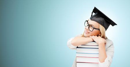 graduacion: la educación, la felicidad, la graduación y la gente concepto - imagen de estudiante feliz en la tapa de la tarjeta del mortero con la pila de libros soñando despierto sobre fondo azul