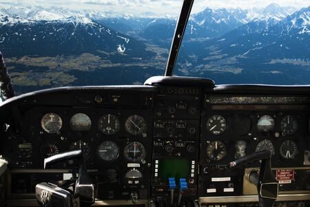 boeing: air transport, travel, technology and aviation concept - dashboard in airplane cockpit and view of snowy alps mountains behind windshield Stock Photo
