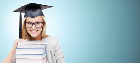 graduacion: la educación, la felicidad, la graduación y la gente concepto - imagen de estudiante feliz en la tapa de la tarjeta del mortero con la pila de libros sobre fondo azul
