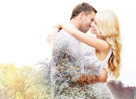 romance: lente, liefde, romantiek, dubbele belichting en dating concept - gelukkig paar knuffelen op kersenbloesem achtergrond Stockfoto