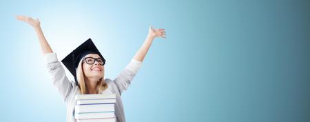 GRADUADO: la educación, la felicidad, la graduación y la gente concepto - imagen de estudiante feliz en la tapa de la tarjeta del mortero con la pila de libros sobre fondo azul