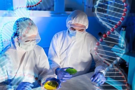la ciencia, la química y la gente concepto - cerca de los científicos con muestras químicas en prueba de toma de placa de Petri o la investigación en laboratorio sobre la estructura de la molécula de ADN