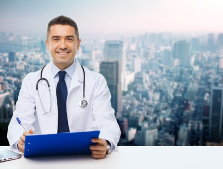 medics: medicine, profession, technology and people concept - happy male doctor with clipboard and stethoscope over city background