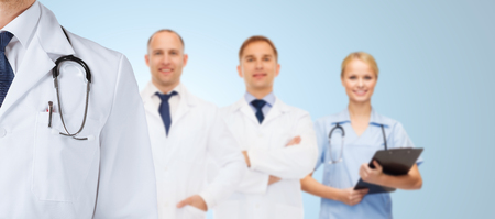 medics: healthcare, profession, teamwork and medicine concept - group of happy medics in white coats over blue background