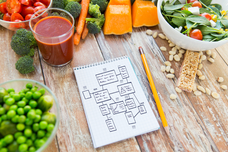 healthy eating, vegetarian food, advertisement and culinary concept - close up of ripe vegetables and notebook with scheme on wooden table Stockfoto