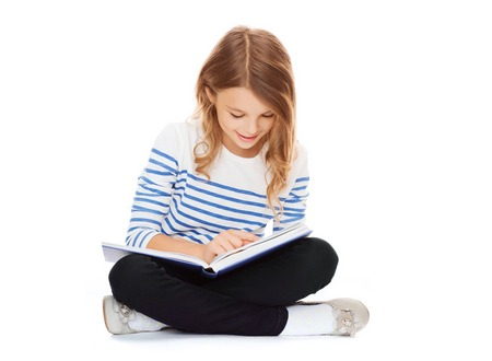 reading: education and school concept - little student girl sitting on floor and reading book