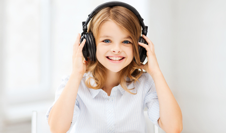 home, technology and music concept - little girl with headphones at home Archivio Fotografico