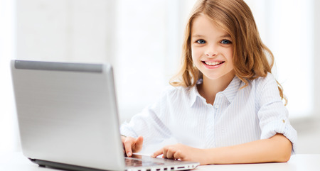 internet school: education, school, technology and internet concept - little student girl with laptop pc at school