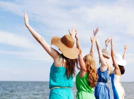 freedom: summer holidays and vacation - girls with hands up on the beach Stock Photo