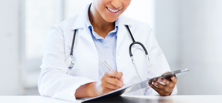 physician: healthcare and medical concept - female doctor with stethoscope writing prescription