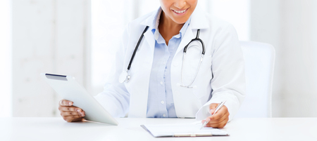 physician: healthcare, medical and technology concept - african female doctor with tablet pc writing prescription Stock Photo