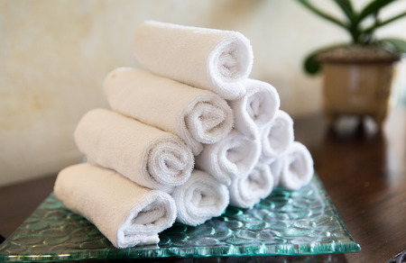 luxury and hygiene concept - rolled bath towels at hotel spa