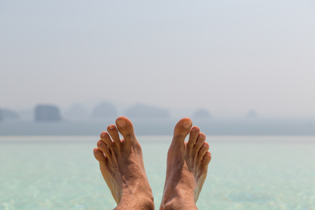 human toe: summer holidays, beach, travel, leisure and body care concept - closeup of male feet over sea and sky Stock Photo