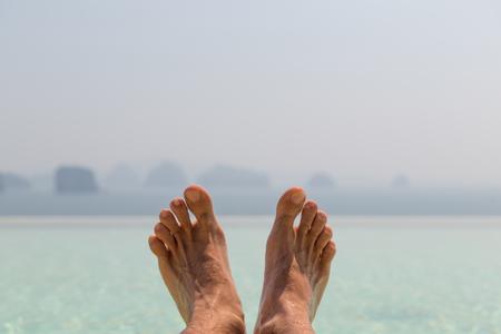 pies masculinos: vacaciones de verano, playa, viajes, ocio y cuidado del cuerpo concepto - primer de pies masculinos sobre el mar y el cielo