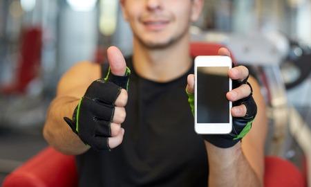 gimnasio: deporte, culturismo, estilo de vida, la tecnolog�a y la gente concepto - hombre joven y feliz con el tel�fono inteligente que muestra los pulgares para arriba en el gimnasio