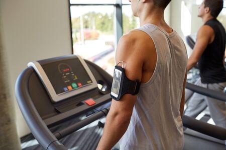 hombres haciendo ejercicio: concepto del deporte, fitness, estilo de vida, la tecnología y las personas - hombres sonrientes que ejercitan en la cinta en el gimnasio