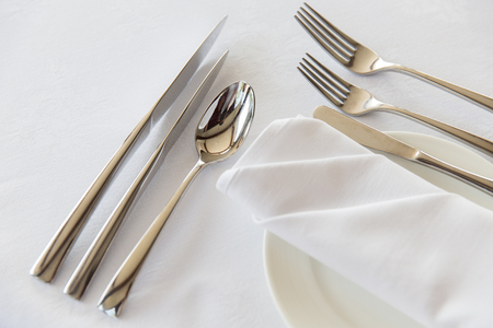 table set: table setting, silverware and eating concept - close up of cutlery set wrapped with napkin and plate on restaurant table Stock Photo