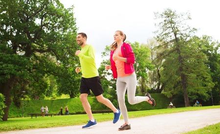 hombre flaco: fitness, deporte, la amistad y el estilo de vida concepto - par sonriente con auriculares correr al aire libre Foto de archivo