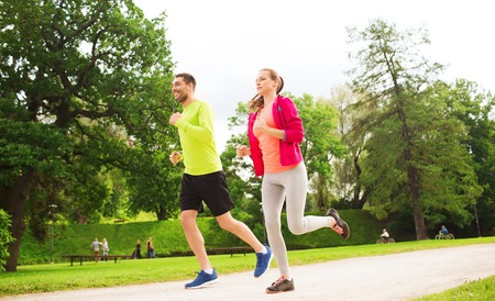 thin man: fitness, sport, friendship and lifestyle concept - smiling couple with earphones running outdoors Stock Photo