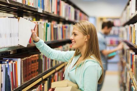 education: 사람, 지식, 교육 및 학교 개념 - 행복 학생 소녀 또는 도서관에서 선반에서 책을 복용하는 젊은 여성