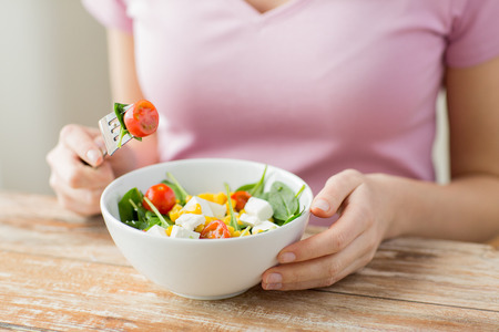 healthy eating, dieting and people concept - close up of young woman eating vegetable salad at home Foto de archivo