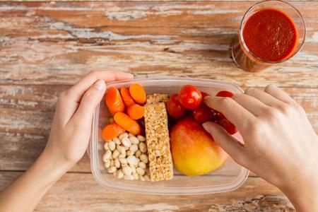 envases plasticos: alimentación saludable, la dieta y el concepto de la gente - cerca de la mujer de las manos con los alimentos en un recipiente de plástico y el jugo de tomate fresco en la cocina de su casa Foto de archivo
