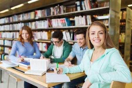 las personas, el conocimiento, la educación y la escuela concepto - niña feliz estudiante que escribe al cuaderno en la biblioteca
