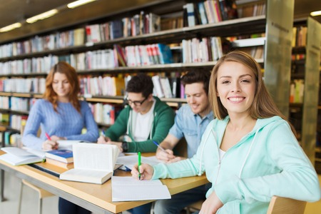 escritura: las personas, el conocimiento, la educación y la escuela concepto - niña feliz estudiante que escribe al cuaderno en la biblioteca