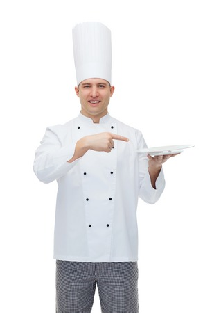 empty of people: cooking, profession, advertisement and people concept - happy male chef cook showing something on empty plate Stock Photo