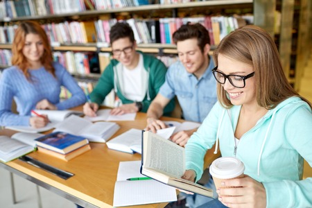 library: people, knowledge, education and school concept - group of happy students reading books, drinking coffee and preparing to exam in library Stock Photo
