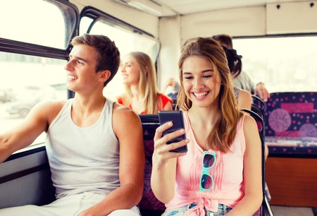 public transport: friendship, travel, summer vacation, technology and people concept - smiling couple with smartphone traveling by tour bus and making selfie