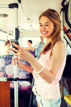 public transfer: travel, vacation, summer, transport and people concept - smiling teenage girl with smartphone going by bus Stock Photo