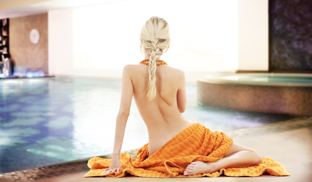 people, beauty, sexuality, spa and luxury concept - beautiful young woman with orange towel over swimming pool background photo