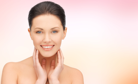 lymph: beauty, people and health concept - beautiful young woman touching her face and neck over pink background