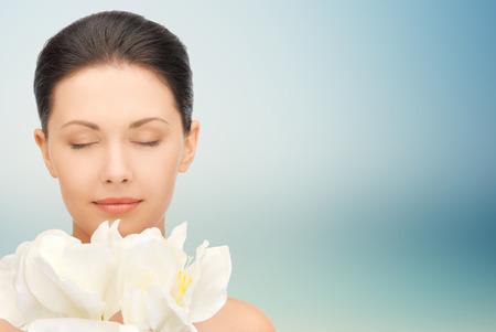 青い背景の上の花の臭いがする美しい若い女性が目を閉じた美、人、休日および健康コンセプト-