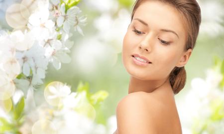 beleza, pessoas e conceito de saúde - belo rosto jovem mulher sobre o verde florescendo fundo do jardim