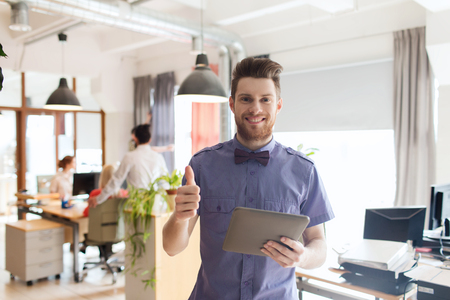 hipster: business, startup and people concept - happy businessman or creative male office worker with tablet pc computer