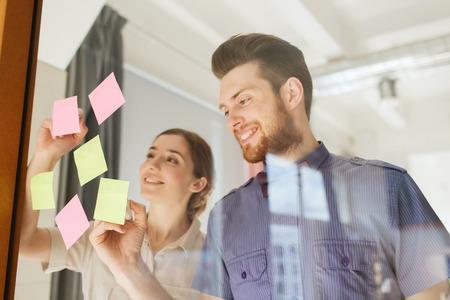 bedrijf, opstarten, planning, management en mensen concept - gelukkig creatieve team schrijven op stickers op het kantoor van glas boord