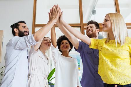 bedrijf, opstarten, gebaar, mensen en teamwork concept - gelukkig creatieve team het maken van hoge vijf in het kantoor