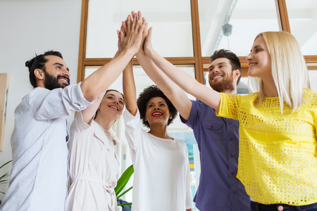 happy business team: business, startup, gesture, people and teamwork concept - happy creative team making high five in office