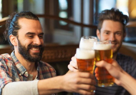 cheers: people, men, leisure, friendship and celebration concept - happy male friends drinking beer and clinking glasses at bar or pub
