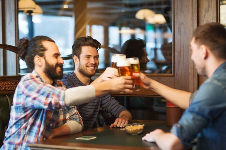 clinking: people, men, leisure, friendship and celebration concept - happy male friends drinking beer and clinking glasses at bar or pub
