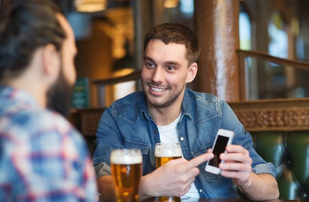 drinks: people, men, leisure, friendship and technology concept - happy male friends with smartphone drinking beer at bar or pub