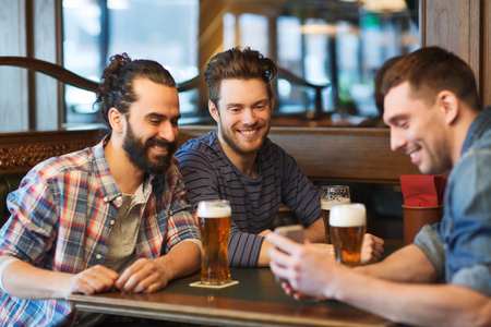 alcoholic drink: people, men, leisure, friendship and technology concept - happy male friends with smartphone drinking beer at bar or pub