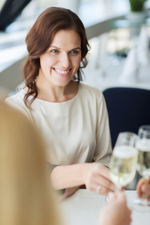 clinking: people, holidays, celebration and lifestyle concept - happy women drinking champagne and clinking glasses at restaurant
