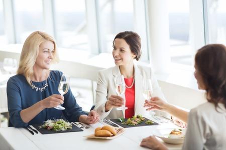 mujeres elegantes: gente, días de fiesta, celebración y el concepto de estilo de vida - felices de las mujeres que beben el champán en el restaurante