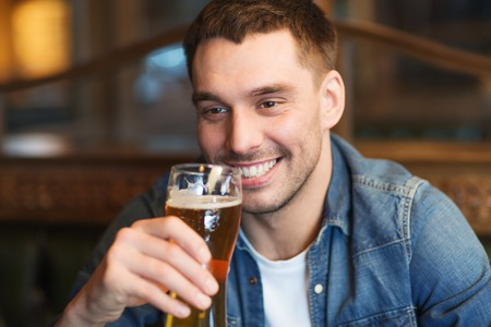 people, drinks, alcohol and leisure concept - happy young man drinking beer at bar or pub Stock Photo