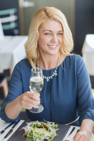 dinner party: people, holidays and lifestyle concept - happy smiling woman drinking champagne at restaurant