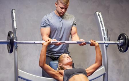 pesas: deporte, gimnasio, trabajo en equipo, el culturismo y la gente concepto - mujer joven y entrenador personal con barra flexionando los músculos en el gimnasio