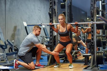 hombre fuerte: deporte, gimnasio, trabajo en equipo, el culturismo y la gente concepto - mujer joven y entrenador personal con barra flexionando los m�sculos en el gimnasio